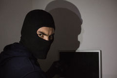 Hacker in balaclava hacking laptop while looking at camera Royalty Free Stock Photo