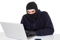 Hacker in balaclava hacking a laptop Royalty Free Stock Image