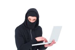 Hacker in balaclava using laptop to steal identity Stock Photo