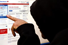 Hacker at Bank of america website. Hacker with covered face trying to gain access at the Bank of America online banking system Royalty Free Stock Photography