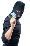 Hacker in black clothes with a bank card in hand on a white. Background Stock Photo