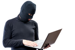 A hacker in black clothes and a mask with a laptop on a white. Background Stock Photos