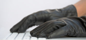 Hacker in black gloves Stock Photography