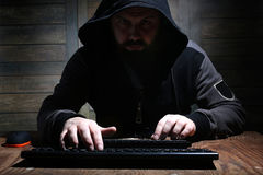 Hacker in the black hood in a room with wooden walls Stock Photo