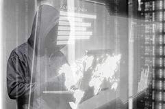 Hacker in black hoodie holding laptop and virtual screen display the server data, binary code, bar graph and world map. Over black background stock images