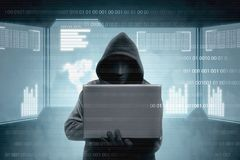 Hacker in black hoodie holding laptop and virtual screen display the server data, binary code, bar graph and world map royalty free stock image