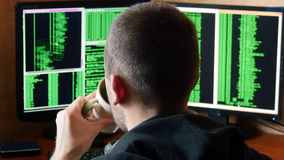 Hacker breaking code and drinking from the cup at your desk. Criminal hacker penetrating network system from his dark Royalty Free Stock Images