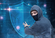 Hacker breaking cyber security protection. Hacker wearing mask breaking cyber security protection Stock Images