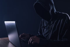 Hacker bypassing hardware firewall on laptop computer. Hooded male cyber criminal Stock Photos