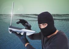 Hacker com capa usando um portátil na frente do campo de número digital imagens de stock royalty free