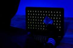 Hacker com cartão de crédito que rouba dados de um portátil na obscuridade fotografia de stock