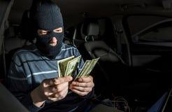 Hacker com um portátil dentro de um carro imagem de stock