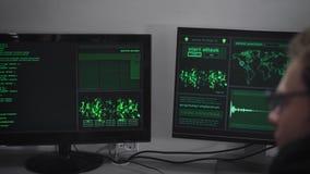 Hacker Company Ein Hacker bereitet sich für einen Cyberangriff vor Ein Mann gibt schnell Informationen ein Auf den Monitoren stock footage