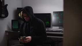 A hacker in the computer room. A man in a jacket with a hood, glasses and money in hands sitting in a chair. A guy with stock video footage