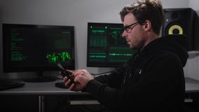 A hacker in the computer room. A man in sunglasses and with a smartphone on hand trying to hack information from foreign. Bases. The room is equipped with all stock footage