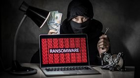 Hacker with computer screen showing ransomware attacking stock image
