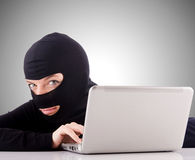 Hacker with computer wearing balaclava Royalty Free Stock Image