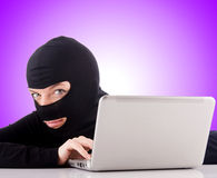 Hacker with computer wearing balaclava Stock Photo