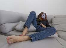Masked man on the couch Stock Images
