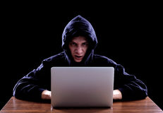 Hacker in a dark hoody sitting in front of a notebook Royalty Free Stock Image