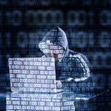 Hacker, der auf einem Laptop schreibt Stockfotografie