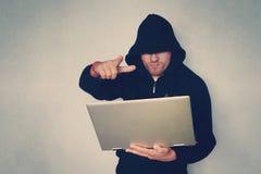 Hacker, der das Gewehr arbeitet an seinem Computerterrorist- und -banditkonzept hält Störschubeffekt- und -kopienraum Schwarzes v lizenzfreies stockfoto