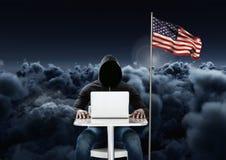 Hacker, der an Laptop nah an der amerikanischen Flagge mit bewölktem Hintergrund arbeitet Stockfotografie