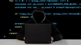 Hacker in der schwarzen Haube mit einem Laptop stock footage