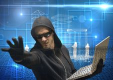 Hacker extending his hand while working on laptop in front of digital blue background Royalty Free Stock Images