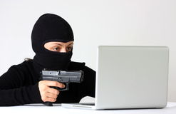 Hacker. Female hacker wit mask pointing a gun on a laptop isolated on a white background Royalty Free Stock Photos