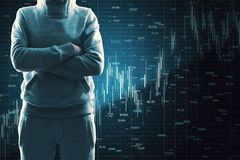 Malware and invest concept. Hacker with folded arms standing on dark background with forex chart. Malware and invest concept royalty free stock photos