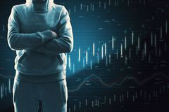 Malware and trade concept. Hacker with folded arms standing on dark background with forex chart. Malware and trade concept royalty free stock photos