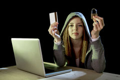 Hacker girl holding credit card violating privacy holding credit card in cybercrime and cyber crime. Young teenager hacker girl in hoodie holding credit card Stock Photos