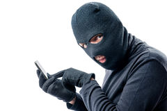 Hacker hacks data from a mobile phone on a white. Background in a mask Royalty Free Stock Images