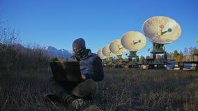 Hacker hacks the radio telescope using notebook. Man to program hacking on laptop in nature. Terrorist is hiding in stock video