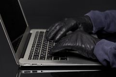 Hacker hand in glove. Working on laptop.Concept of internet criminal hacking stock photos