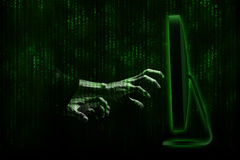 Hacker. Hands with binary codes on monitor stock image
