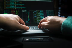 Hacker hands, first person view, at work with interface and stolen credit card. Royalty Free Stock Photos