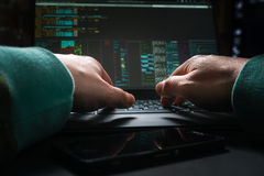 Hacker hands, first person view, at work with interface and stolen credit card. Hacker hands at work with interface around Stock Photos