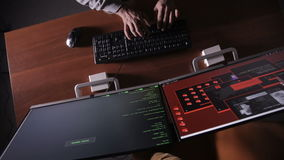 Hacker hands at night typing on a computer keyboard hacking secret information. stock footage