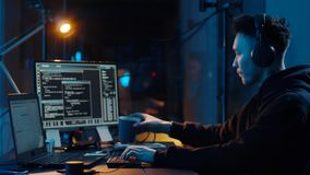 Hacker in headphones using laptop computer at nigt. Cybercrime, hacking and technology concept - asian male hacker in headphones with coding on laptop computer stock footage
