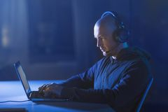 Hacker in headset typing on laptop in dark room Royalty Free Stock Photo