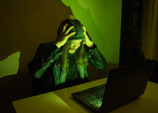 Hacker on his computer is going crazy because he got cought Royalty Free Stock Photos