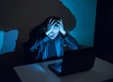 Hacker on his computer is going crazy, pulling his hair, because he got cought Royalty Free Stock Photography