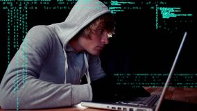 Hacker on his laptop. Close up of a Caucasian male hacker wearing a hoodie and gloves while working on a laptop. Interface codes are moving in the background stock video footage