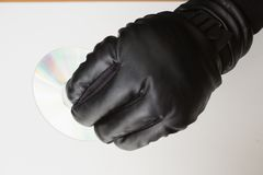 Hacker holding a cd-ro. On white background Stock Photos