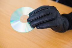 Hacker holding a cd rom. Over wooden desk Royalty Free Stock Image