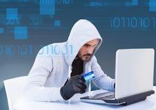 Hacker holding a credit card and using a laptop in front of blue digital background. Digital composite of hacker holding a credit card and using a laptop in Royalty Free Stock Image