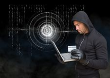 Hacker holding a credit card and using a laptop in front of digital background Stock Photography