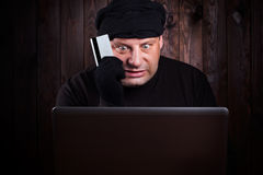 Hacker holding a credit card Royalty Free Stock Photos